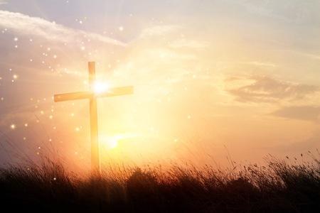 Silueta de la cruz cristiana sobre el césped en el fondo del amanecer con la iluminación brillante milagrosa, la religión y el concepto de adoración Foto de archivo