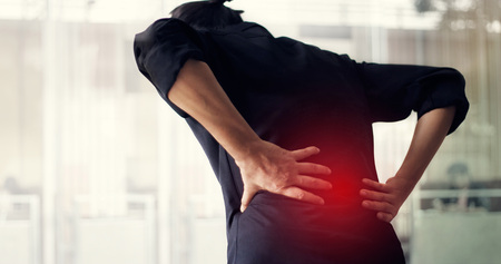 Mężczyzna cierpiący na ból pleców z powodu zespołu biurowego, jego dłonie dotykają dolnej części pleców. Koncepcja medyczna i zdrowotna