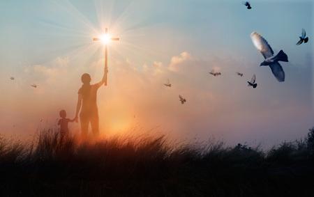 Silhouette de prières chrétiennes mère et fils soulevant croix tout en priant Jésus sur fond de coucher de soleil, concept de culte