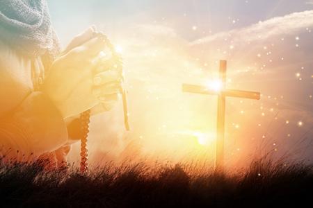Exposición doble. Mujer rezando con cruz sobre fondo de puesta de sol de naturaleza, concepto de esperanza Foto de archivo