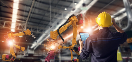 모니터링 시스템 소프트웨어에서 산업용 지능형 공장에서 태블릿 검사 및 제어 자동화 로봇 팔 기계를 사용하는 엔지니어. 용접 로봇 및 디지털 제조 작업. 스톡 콘텐츠