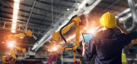 Ingeniero que usa la máquina de brazos de robot de automatización de control y verificación de tabletas en una fábrica inteligente industrial en el software del sistema de monitoreo. Robótica de soldadura y operación de fabricación digital. Foto de archivo