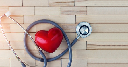 Medical concept, red heart and stethoscope on wooden background. The symbolic equipment for specialized doctor in cardiovascular desease. 스톡 콘텐츠