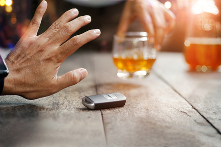 Man hand with car key on table rejecting glass with alcoholic beverage on blurred friend background Stock Photo