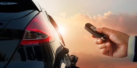 Close-up zakenman hand ontgrendeld de auto met afstandsbediening op parkeren zonsondergang achtergrond