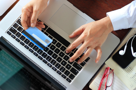 Business woman using laptop with credit card in hand. Online payments, banking, Shopping. on top view. Stockfoto