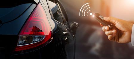 Close-up zakenman hand auto sleutel afstandsbediening te ontgrendelen met teken pictogram