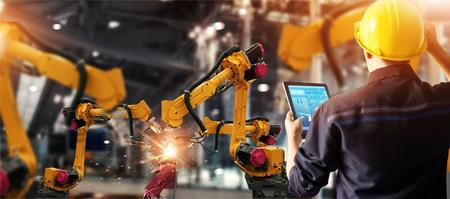 Inżynier sprawdza i kontroluje automat spawalniczy z automatycznymi ramionami w inteligentnej fabryce motoryzacyjnej z oprogramowaniem systemu monitorowania. Cyfrowa operacja produkcyjna. Przemysł 4.0 Zdjęcie Seryjne