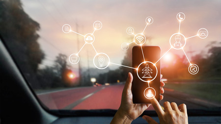 Man using mobile smartphone with icon, device processing network connection and communication in car on street on sunset background. Technology and telecommunication concept. Фото со стока