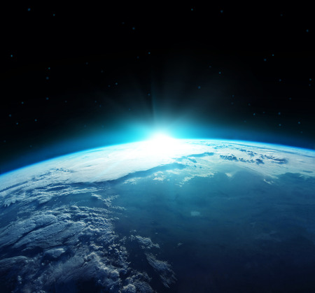 View of blue planet Earth with sun rising from space.