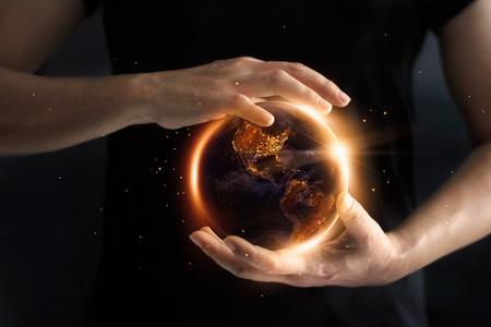 Manos sosteniendo global que muestra el consumo de energía por la noche, el medio ambiente y el concepto de conservación de energía. Día de la Tierra. Foto de archivo