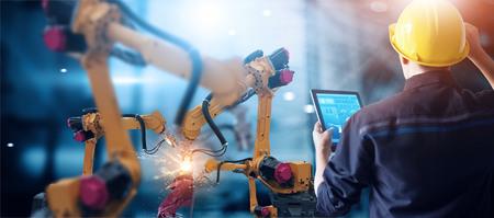 Ingénieur vérifie et contrôle la machine automatique de bras de robotique de soudure dans l'industrie automobile intelligente d'usine avec le logiciel de système de surveillance. Opération de fabrication numérique. Industrie 4.0