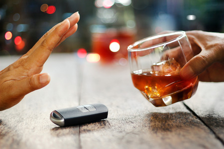 Man hand with car key on table rejecting glass with alcoholic beverage on colorful background