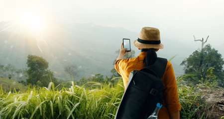 backpack using smartphone taking picture beautiful landscape on mountain peak while exploring, trekking in tropical rain forest of Asia