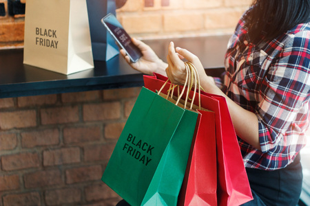 Black Friday, Woman using smartphone and holding shopping bag while sitting in the mall background 版權商用圖片 - 109472561