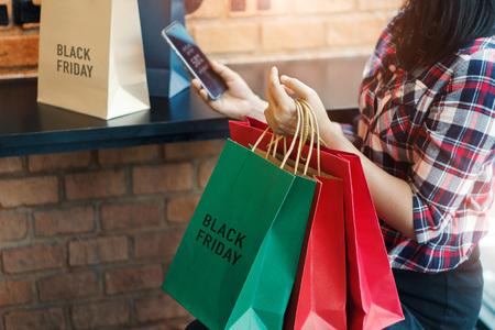 Viernes negro, mujer con teléfono inteligente y sosteniendo la bolsa de compras mientras está sentado en el fondo del centro comercial