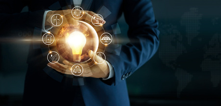 Businessman' s hand holding glowing light bulb with energy sources icon. Campaigning for ecological friendly and sustainable environment. Earth day. Energy saving concept Stok Fotoğraf