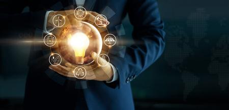 Mano de hombre de negocios que sostiene la bombilla incandescente con el icono de fuentes de energía. Hacer campaña por un medio ambiente ecológico y sostenible. Día de la Tierra. Concepto de ahorro de energía