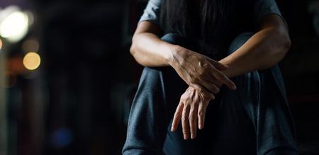 PTBS-Konzept für psychische Gesundheit. Posttraumatische Belastungsstörung. Die depressive Frau, die allein auf dem Boden im Hintergrund des dunklen Raumes sitzt. Filmlook.