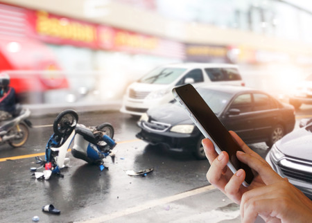 Dangerous traffic on the road, Careless driving car collides with motorcycle. Woman hands using smartphone calling ambulance and car insurance service. Concept of car accidents, emergency and insurance concept