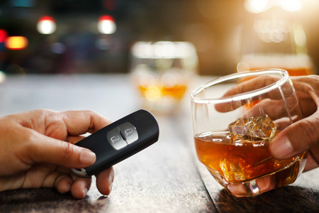 Hand holding alcoholic drink, another hold car remote, Drunk driving concept. Stock Photo