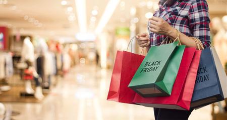 Black Friday, vrouw met veel boodschappentassen tijdens het wandelen op de achtergrond van het winkelcentrum. Stockfoto