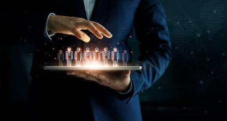 Businessman holding tablet and management group of people in his hand. Virtual icon of social network. Business technology concept. Фото со стока - 109473037