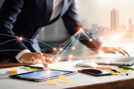 Biznesmen dotyka tabletu i laptopa. Zarządzanie globalną strukturą sieciową i wymianą danych połączenia z klientami w miejscu pracy. Technologia biznesowa i koncepcja sieci marketingu cyfrowego.