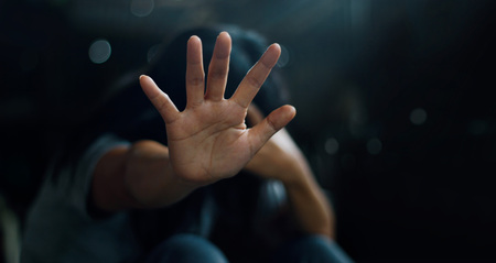 PTSD Mental health concept. Post Traumatic Stress Disorder. The depressed woman sitting alone on the floor and waving refusal to help from people in the dark room background. Film look. Soft focus. Stock Photo