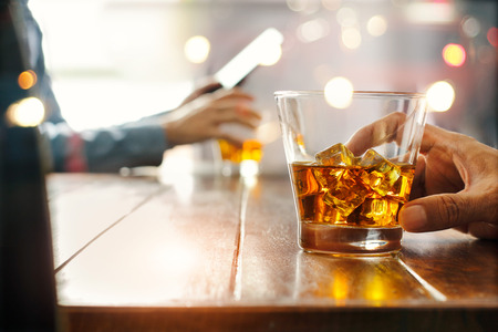 Close-up of two men of whiskey drink alcoholic beverage at bar counter in the pub background.