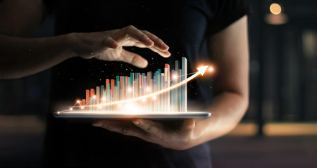businessman holding tablet and showing a growing virtual hologram of statistics, graph and chart with arrow up on dark background. Stock market. Business growth, planing and strategy concept. 免版税图像