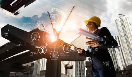 A futuristic architect, Businessman, Industry 4.0. Engineer manager using tablet with icon network connection in construction site, Industrial and innovation. Industry technology concept. Banco de Imagens