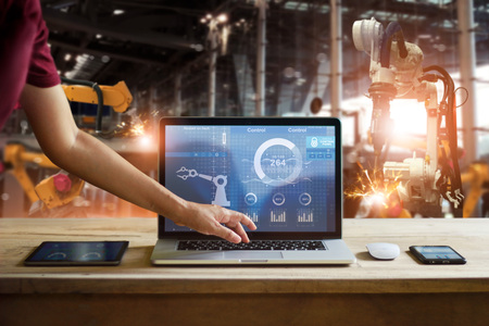 Engineer touching laptop check and control welding robotics automatic arms machine in intelligent factory automotive industrial with monitoring system software. Digital manufacturing operation.Industry 4.0 Standard-Bild