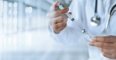 Lekarz medycyny i strzykawka z dawką szczepionki przeciw grypie w laboratorium, mikrobiologii i badaniach farmaceutycznych, medycynie i opiece zdrowotnej.