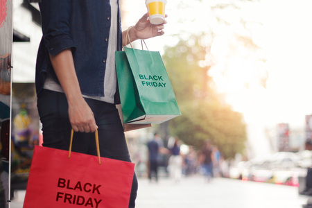 Black Friday, Women with coffee cup in hand and holding shopping bag while standing on the mall background. Stock Photo