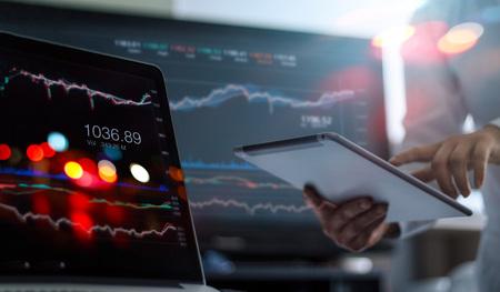 Geschäftsmann, der Tablet und Laptop zur Analyse von Datenbörsen im Überwachungsraumhintergrund verwendet, Devisenhandelsdiagramm, Börsenhandel online, Finanzinvestitionskonzept. Alle auf dem Laptop-Bildschirm sind designt.
