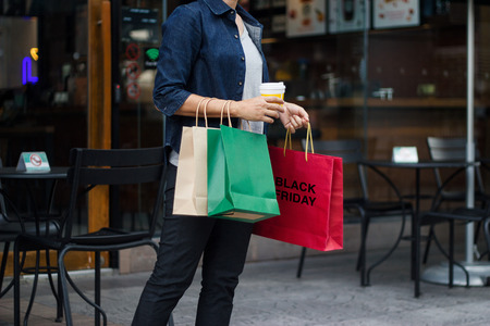 Black friday. Women with coffee cup in hand and holding shopping bag while walking on the shopping mall background.