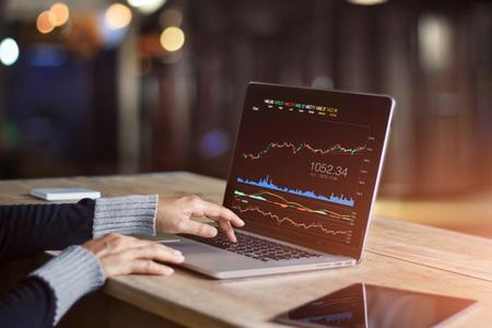 Hombre de negocios usando la computadora portátil para analizar el mercado de valores de datos, gráfico de comercio de divisas, comercio de bolsa en línea, concepto de inversión financiera. Todo en la pantalla del portátil está diseñado.