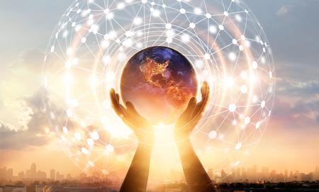 Scienza astratta. Mani che toccano la terra e circondano la connessione di rete globale, scambi di dati in tutto il mondo sullo sfondo del tramonto della città. Innovazione. Creativo e ispirazione. Idea e fantasia. Concetto di rete e tecnologia