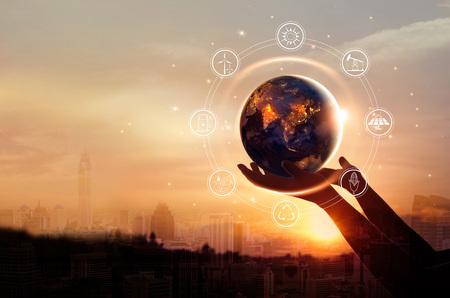 La terre la nuit tenait dans des mains humaines avec l'icône des ressources énergétiques sur fond de ville. Jour de la Terre. Concept d'économie d'énergie.