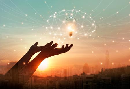 Ciencia abstracta. Mano que sostiene la red digital del cerebro y la bombilla dentro de la conexión de red en el fondo de la ciudad. Idea e imaginación. Creativo e inspirador. Tecnología de innovación Foto de archivo