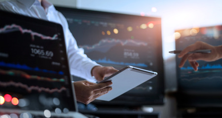 Business team working together. Businessman using tablet for analyzing data stock market in monitoring room with team pointing on the data presented in the chart on screen, forex trading graph, stock exchange trading online, financial investment concept. All on laptop screen are design up.