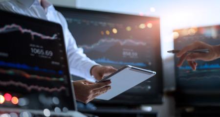 Geschäftsteam, das zusammenarbeitet. Geschäftsmann, der Tablet zur Analyse von Datenbörsen im Überwachungsraum verwendet, wobei das Team auf die im Diagramm auf dem Bildschirm dargestellten Daten zeigt, Devisenhandelsgrafik, Online-Börsenhandel, Finanzanlagekonzept. Alle auf dem Laptop-Bildschirm sind designt.