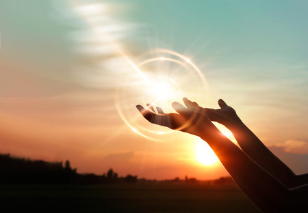 Woman hands praying for blessing from god on sunset background Archivio Fotografico