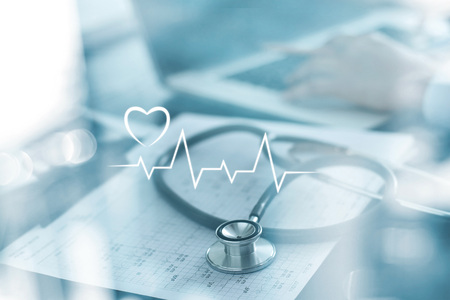 Stethoscope with heart beat report and doctor analyzing checkup on laptop in health medical laboratory background