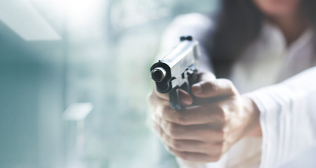 Woman pointing a gun at the target on blur background, criminal with gun, selective focus on front gun.