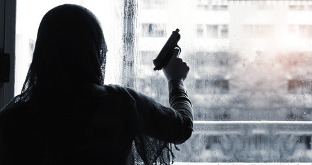 Terrorist criminal with gun in hand on building, rain drop background. Black and white.