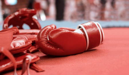 Red boxing gloves and boxing head guards for martial arts on pad background. Stock Photo - 119057903