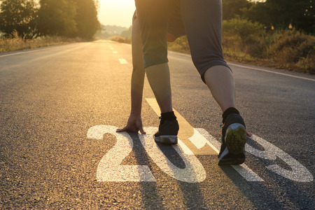 Healthy way of life new year concept. goals and plans, Healthcare and medical. Woman in sports wear running start to goals new year 2019 on the road in sunset background. Stock Photo