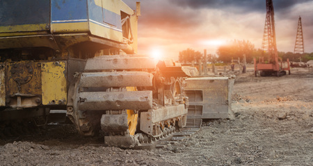 Old excavator with crane on construction site ,construction worker, industry equipment on sunset background,